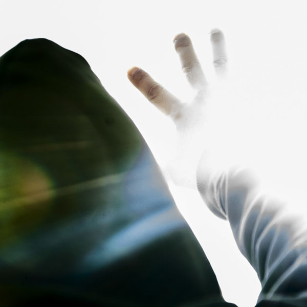 Person in hoodie reaching for the light