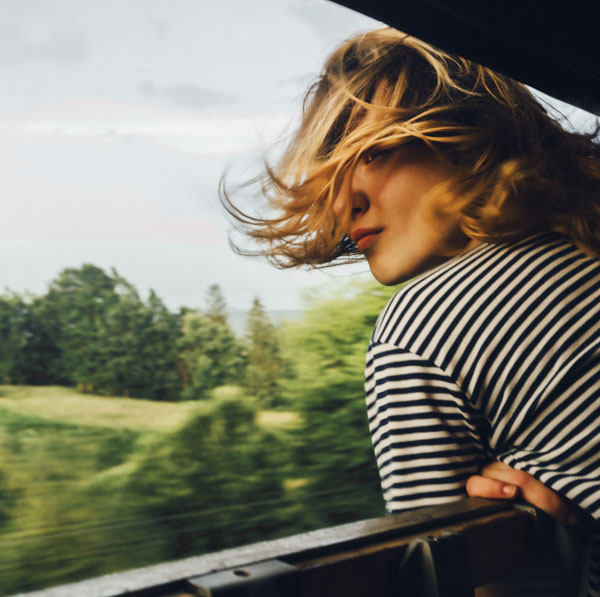 Woman looking out open window of train