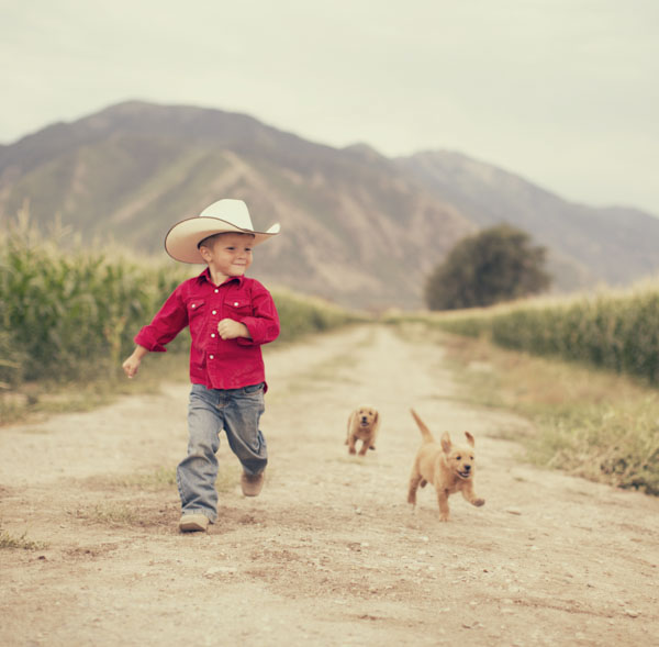 Little cowboy running gleefully with his dogs