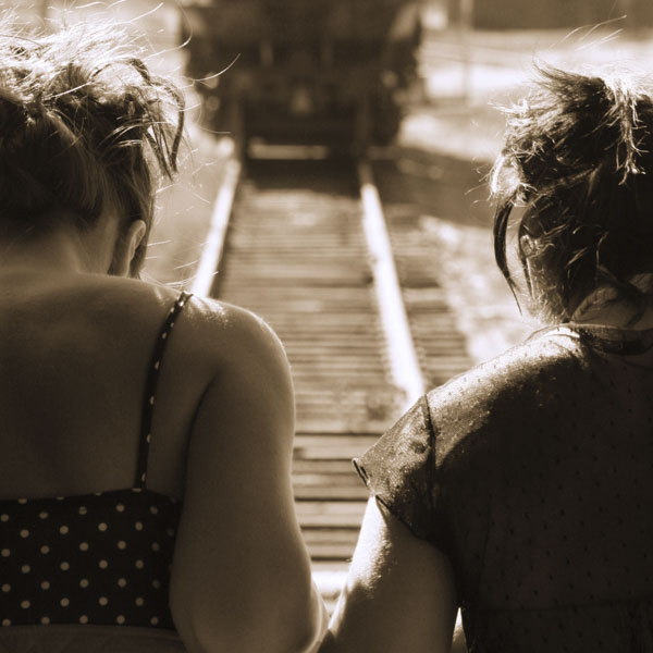 Two friends walking on train tracks