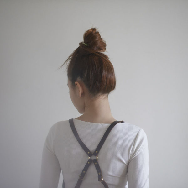 Woman with suspenders crisscrossed in back