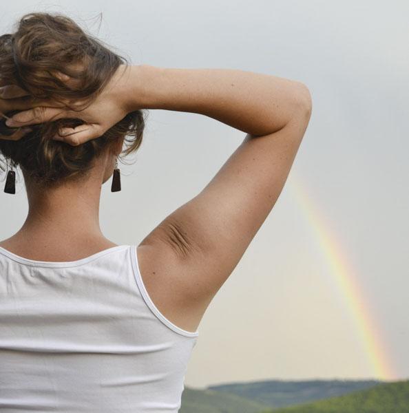 Woman looking at rainbow on horizon