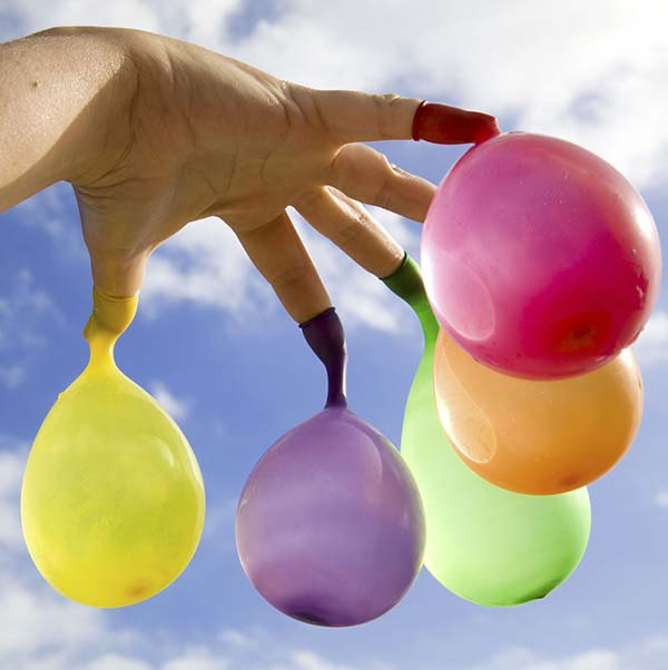 Fingers on hand holding multi colored water balloons