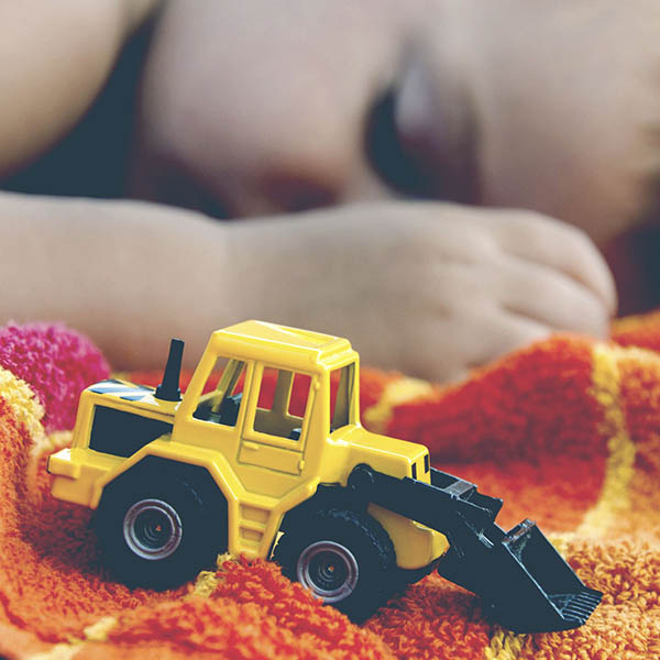 Little boy asleep on beach towel with excavator