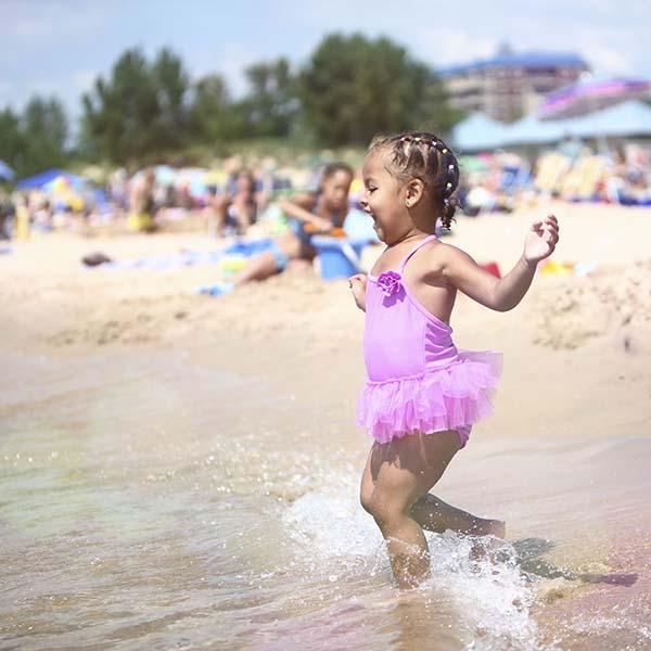 Little girl running into waves
