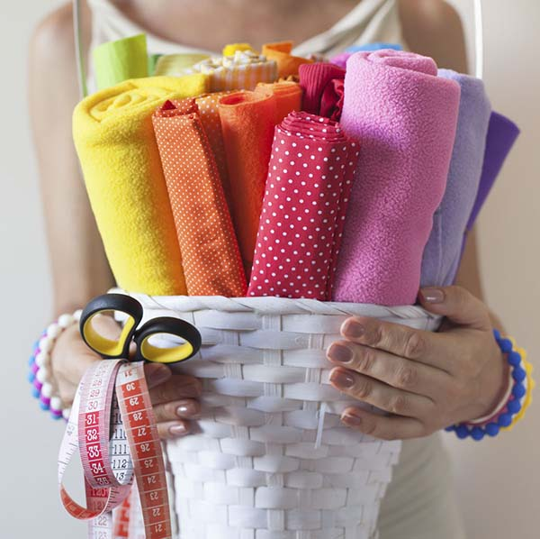 Woman holding basket of fabric scraps