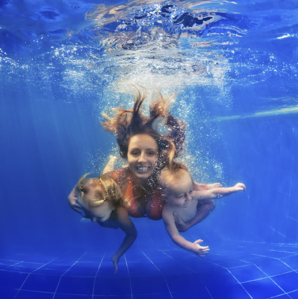 Mother swimming underwater with her babies