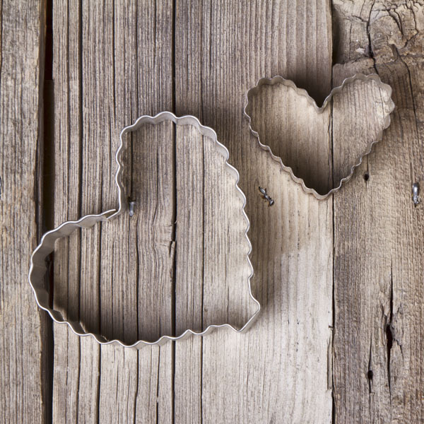 Tin heart-shaped cookie cutters on wood