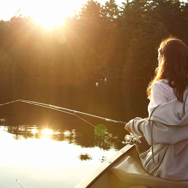 Girl with fishing rod on a lake