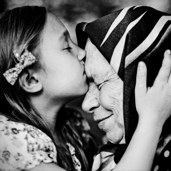 Little girl kissing grandmother's forehead