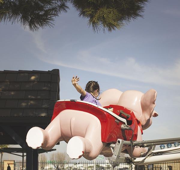 Little girl riding elephant ride at theme park