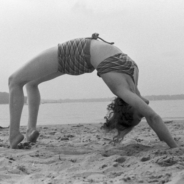 Woman bending backwards on beach