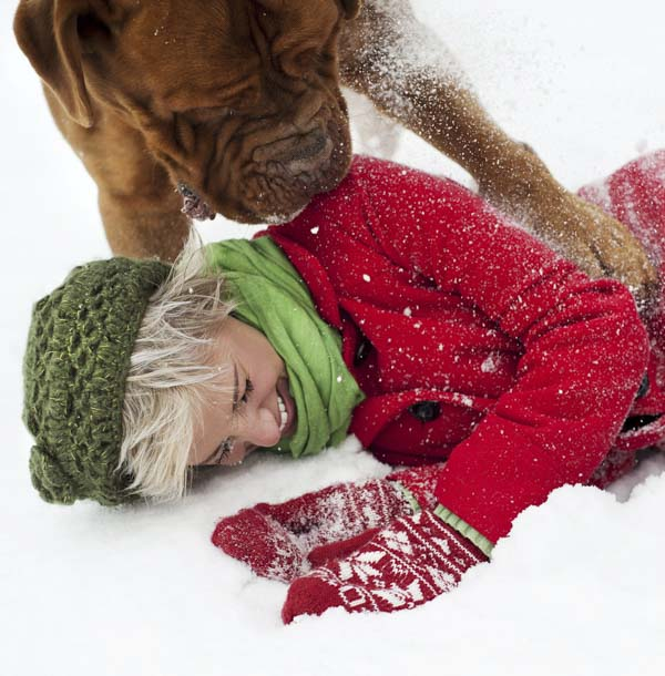 Woman and dog playing in snow