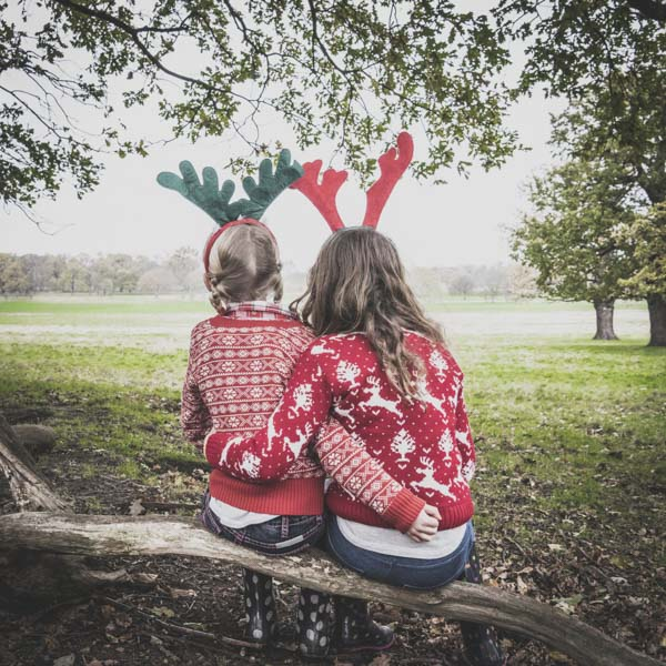 Two friends with Christmas sweaters and reindeer ears