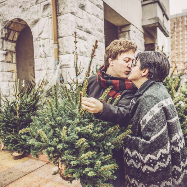 Couple kissing and holding small Christmas tree
