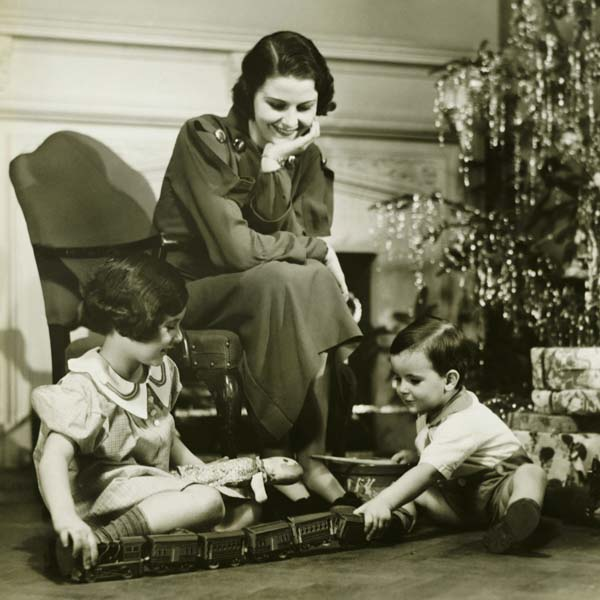 Vintage mother watching her children play with toy train on Christmas morning