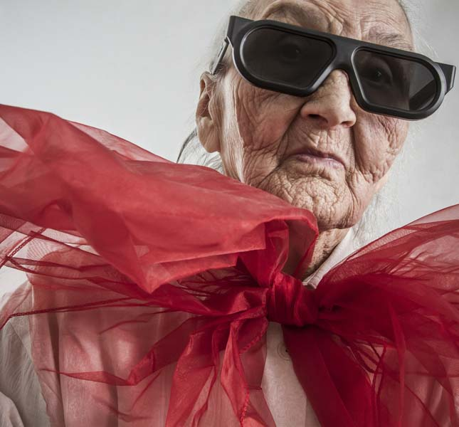 Old wrinkled woman with sunglasses and big red bow