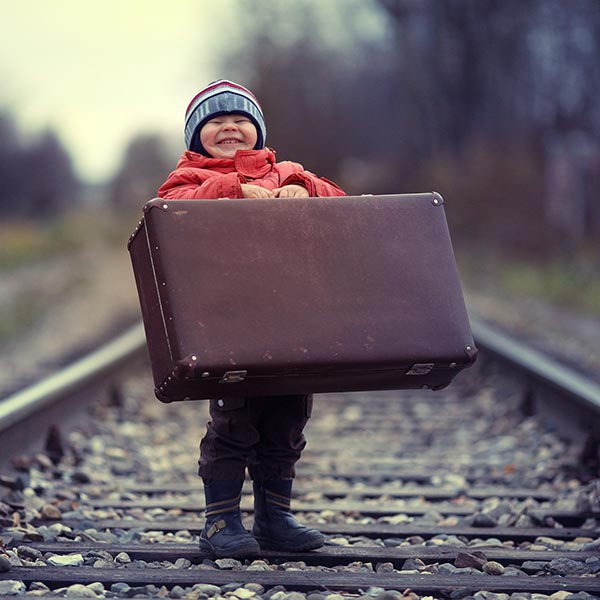 Little girl on train tracks with big grin holding suitcase