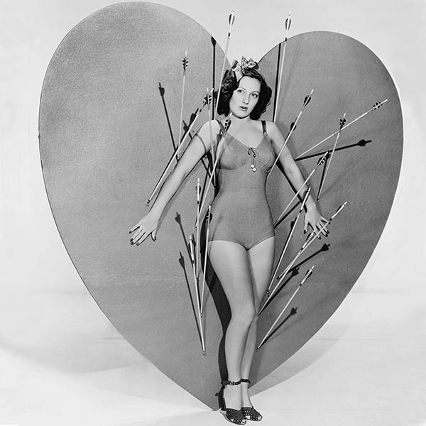 Vintage woman standing against heart with arrows