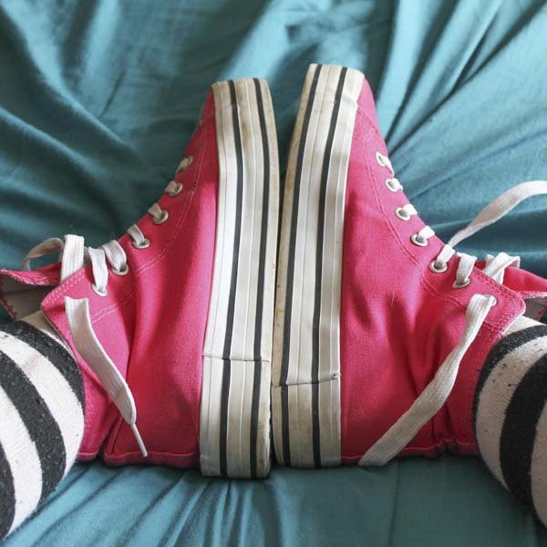 Pink high top sneakers heel to heel