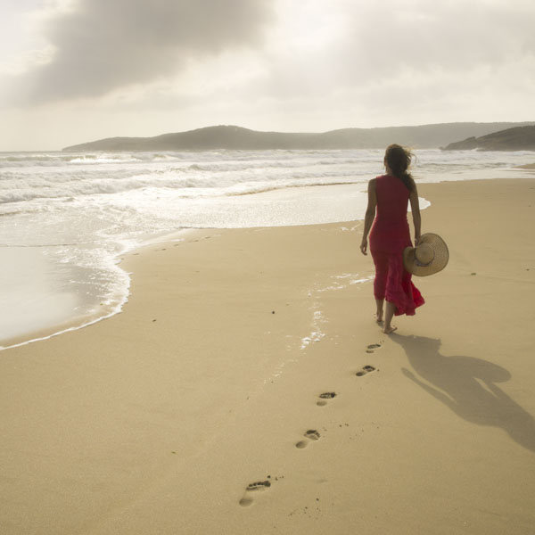 Woman walking down the beach leaving footprints