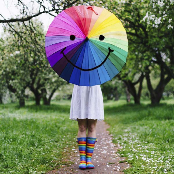 Girl holding rainbow umbrella with smiley face