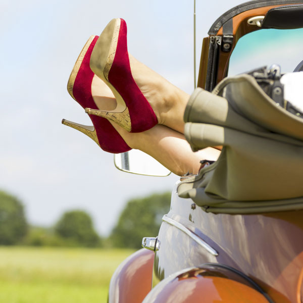Woman in red heels kicking back in convertible