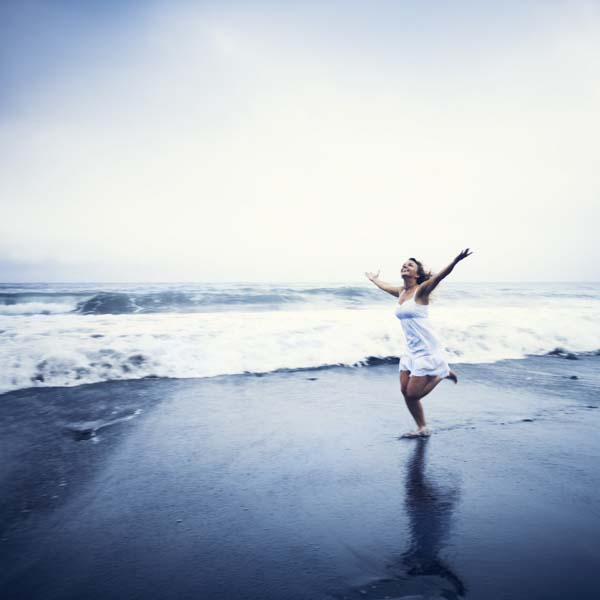 Woman running with arms wide open on beach
