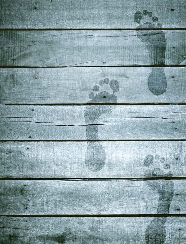 Wet footprints on blue pier