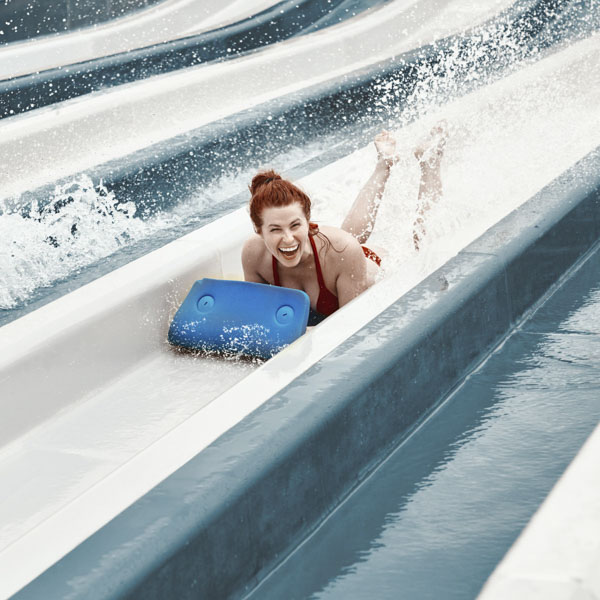 Woman sliding down a water slide laughing