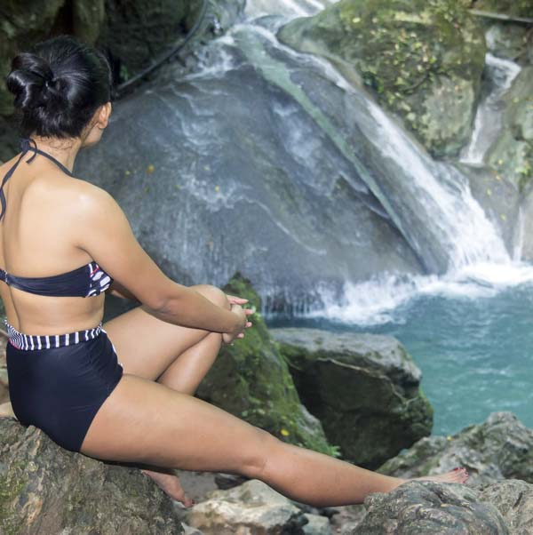 Woman in bathing suit watching waterfall