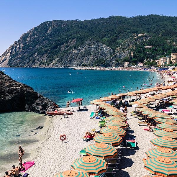 Weekend beach scene with dozens of umbrellas
