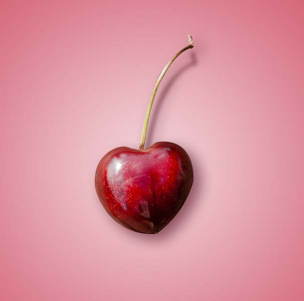 Heart-shaped cherry on pink background