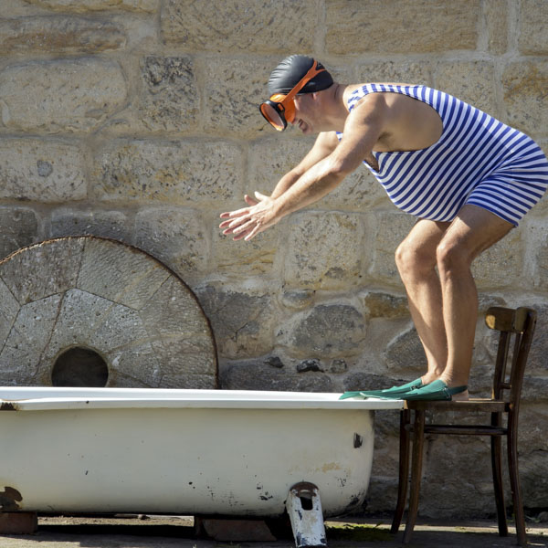 Vintage swimmer diving into bathtub