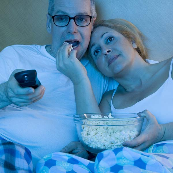 Couple in bed watching TV