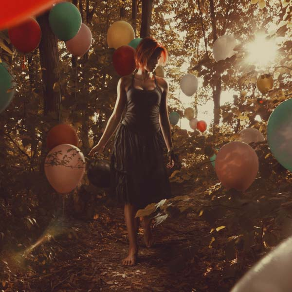 Woman walking through forest with balloons