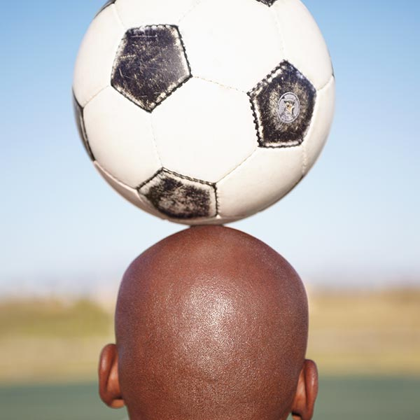 Man balancing soccer ball on his head