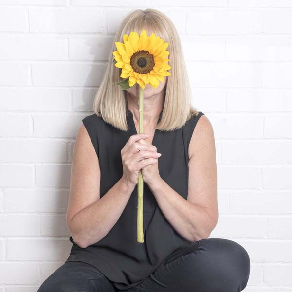 Mother holding up sunflower in front of face