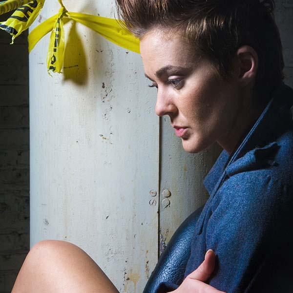 Woman sitting near caution tape