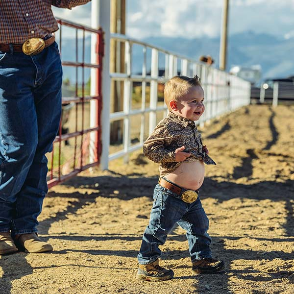 Baby cowboy with big smile and big belly