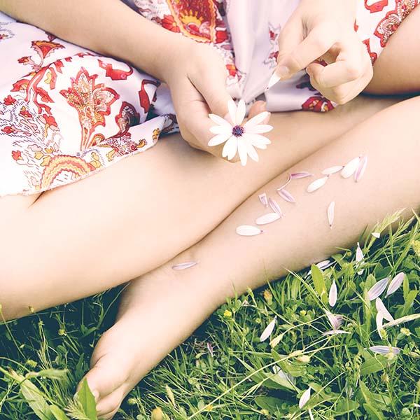 Girl picking daisy flower apart