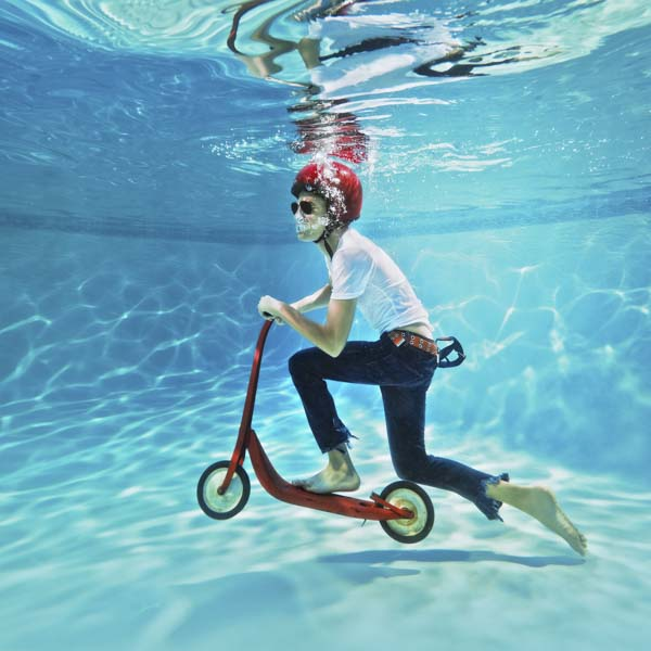 Boy riding a scooter underneath the water