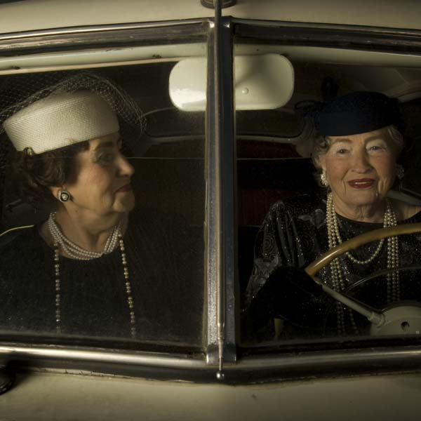 two ladies dressed up sat in a car