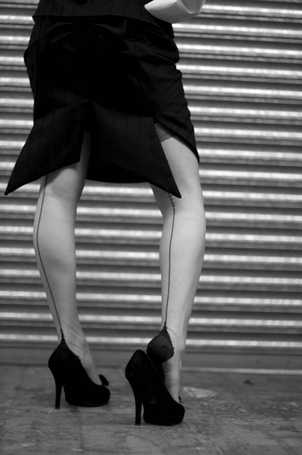 Woman's legs wearing a black skirt, transparent stockings and black high heels