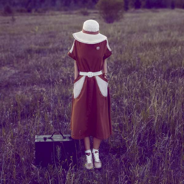 Woman in a field with face covered by a hat next to a black briefcase