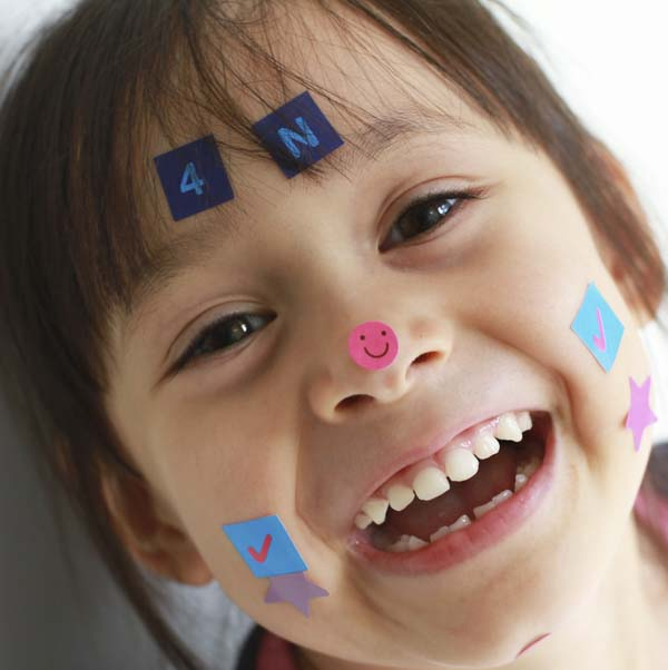 Little kid smiling away with stickers on her face
