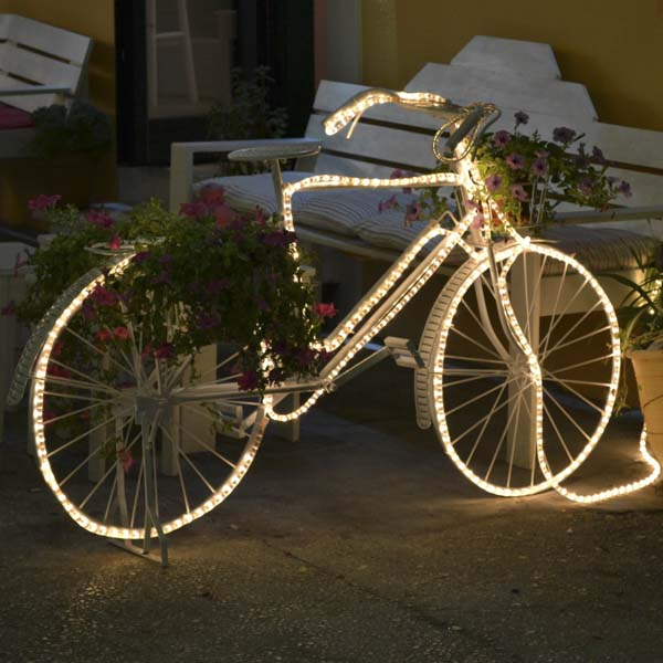 Bike with rope lights parked near a bench