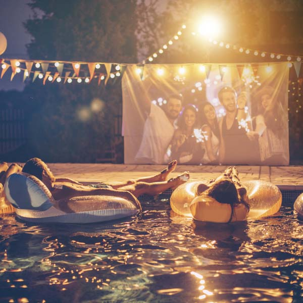 Couple laying on a floater watching a movie on a big screen