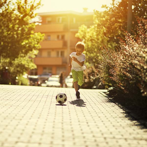 A boy playing with ball in the street