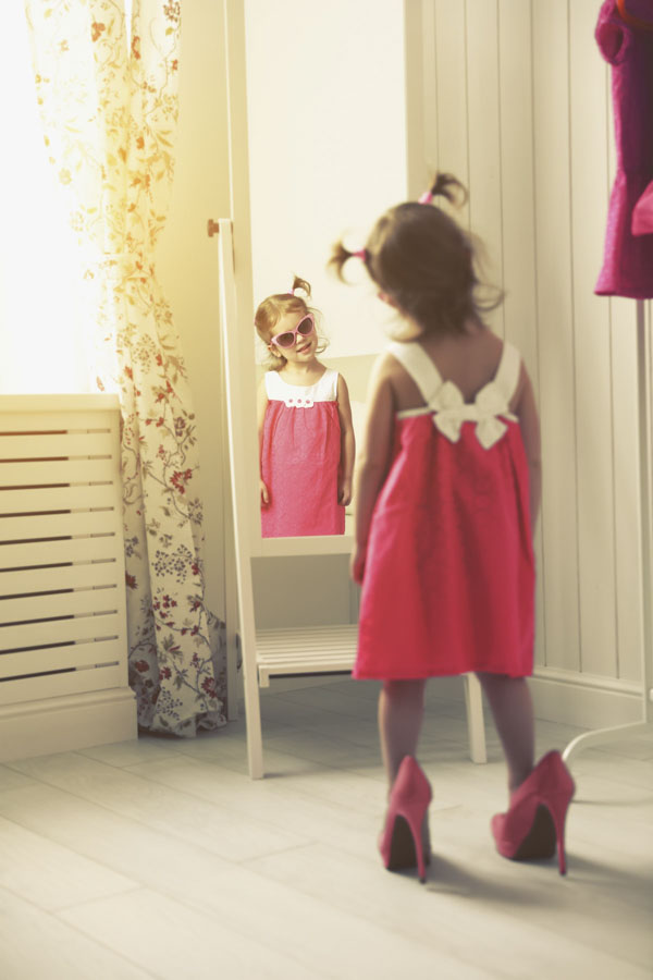 Little girl looking herself in the mirror wearing a pink dress, sunglasses and a pink oversize high heels shoes